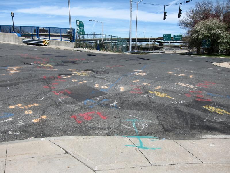 Eine Straßenkreuzung übersät mit Graffiti welche auf Straßeneinbauten hinweisen