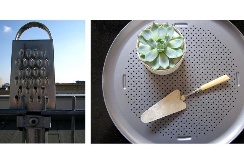 Eine Küchenreibe an einem Zaun und eine Kuchenschaufel nebst Pflanze auf einem runden Kuchenblech