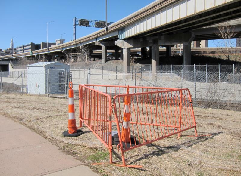 Eine Autobahnbrücke über ein Bahngleis, davor drei Absperrgitter im Dreieck, darin ein Plastikpoller und vor den Gittern steht ein weiterer und sieht hinein