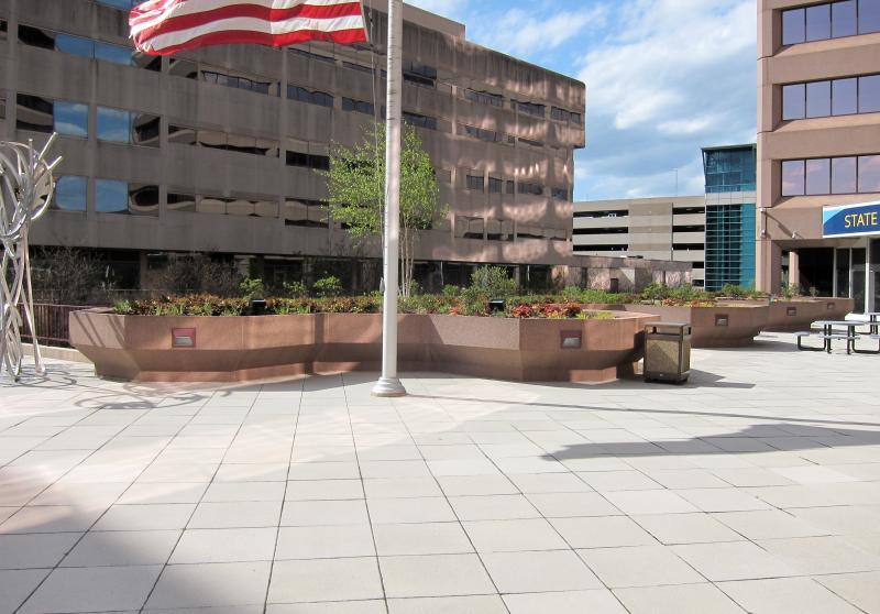 Bürogebäude, Hochbeete, Kunst im öffentlichen Raum und eine US-Flagge auf Halbmast
