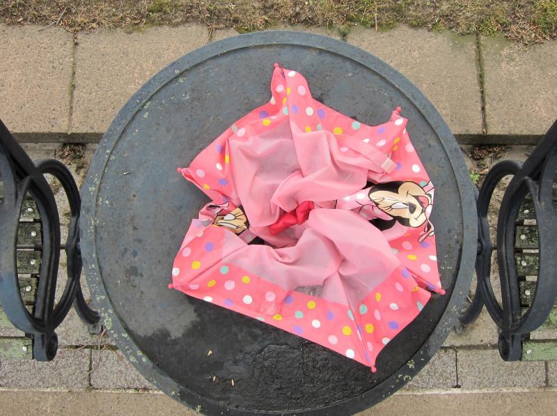 Ein kaputter rosafarbener Regenschirm mit Minimaus in einer Mülltonne