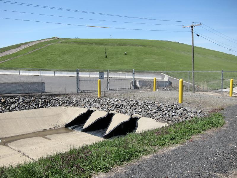 Eine stillgelegte Mülldeponie mit Drainage, Zaun, Pollern, Strommast und Leitungen