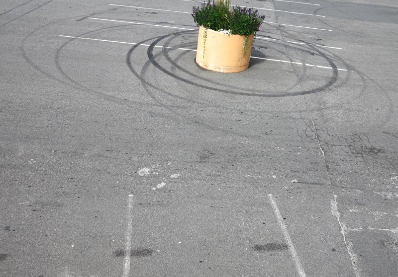 Ein Pflanztrog auf einem Parkplatz umkreist von exzentrischen Reifenspuren